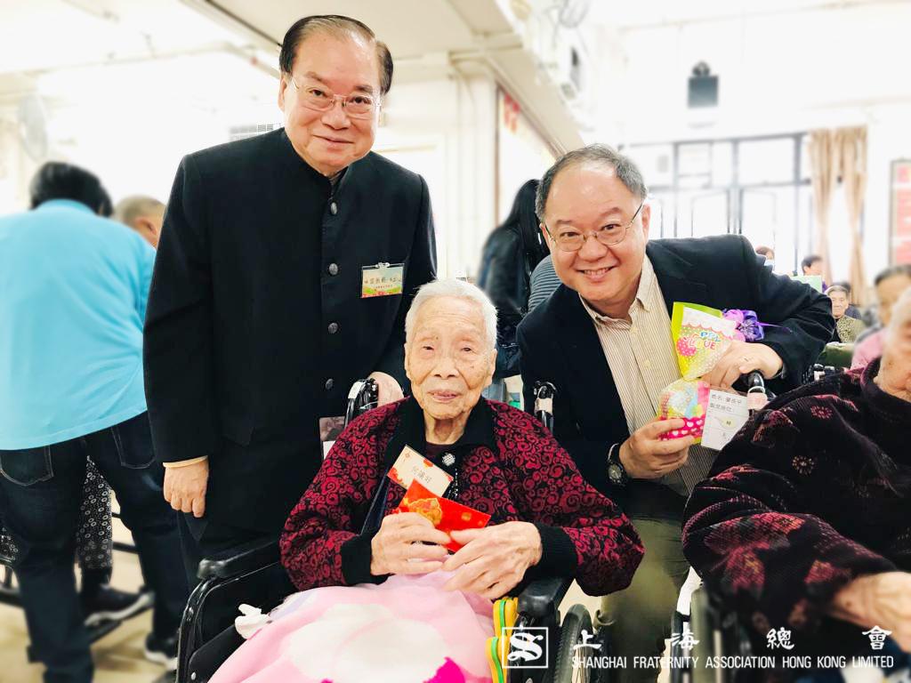 雷振範副理事長、葉青山先生一邊派發利是,一邊與院友合照。